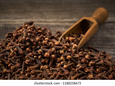 Dried cloves in a wooden shovelon a gray wooden background