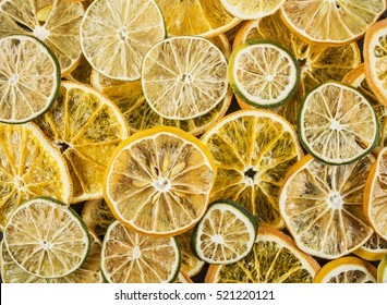 Dried colorful slices of lemon, the lime and orange background, close up