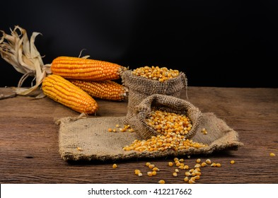 Dried corn seeds in sack bag on wooden board,agriculture product