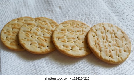 Dried crackers in a line on a white surface.
