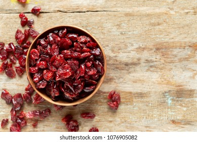 dried cranberries in bowl on wooden table