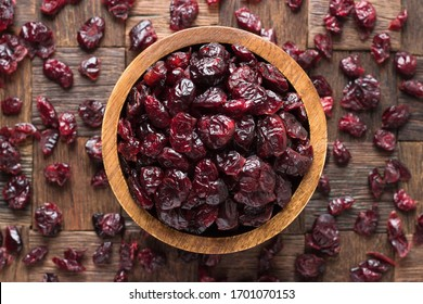 dried cranberries in bowl on wooden table background.
