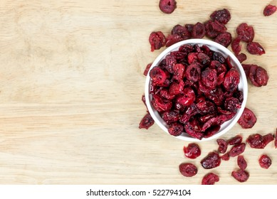 dried cranberries in a bowl on wooden background.