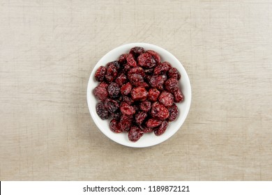 Dried cranberries in white bowl on gray wooden background.