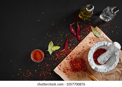 Dried and crushed red chili pepper in stone mortar. Copy space