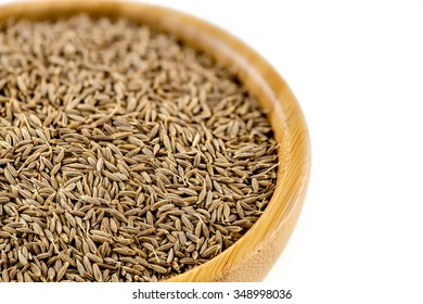Dried cumin seeds in a wooden container against white background.