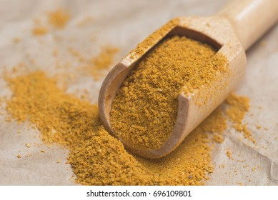 dried curry powder  in measuring spoon on paper background