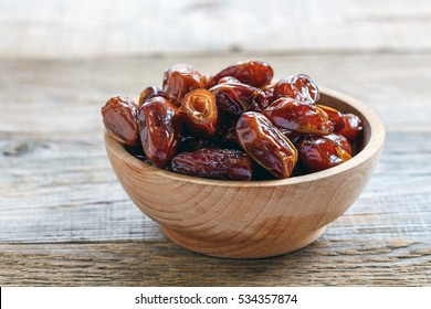 Dried date fruit in bowl on the old wooden table.