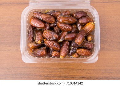 Dried date fruits in plastic container on wooden table. Top view