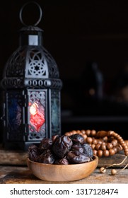 Dried date fruits in wooden bowl. Selective focus.
