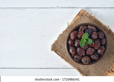 dried date and green mint in a bowl on white wooden table. dates fruit or kurma for breaking the fast in ramadan