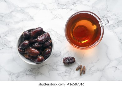 Dried dates with cup of tea on marble table. Traditional arabic food. Ramadan event. Top view