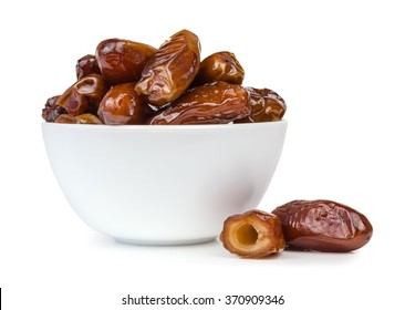 Dried dates fruit in a bowl, isolated on a white background