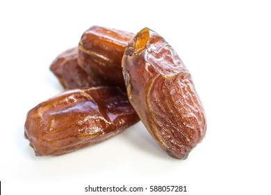 Dried dates fruit over a white background.