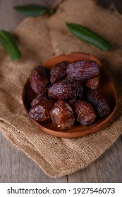Dried dates fruits in a plate on old wooden table close up. Ramadan Kareem
