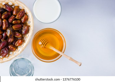 Dried dates, milk and honey on white background. Holy month of Ramadan, concept. Righteous Muslim lifestyle. Starvation. Dates in wooden basket and honey. Vegetarian food. Copy space