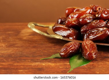 Dried dates on metal tray on wooden background