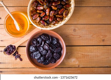 Dried dates, prunes and honey on wooden background. Holy month of Ramadan, concept. Righteous Muslim lifestyle. Starvation. Dried fruits: dates, prunes and raisins on wooden boards