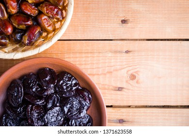 Dried dates and prunes on wooden background. Holy month of Ramadan, concept. Righteous Muslim lifestyle. Starvation. Dried fruits: dates, prunes and raisins on wooden boards