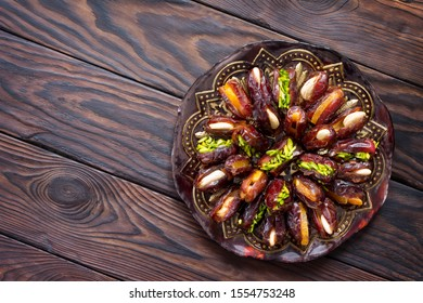 Dried dates stuffed with candied fruits and nuts on a rustic wooden table. Top view flat lay background with copy space.