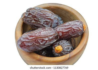 Dried dates in a wooden bowl isolated on white