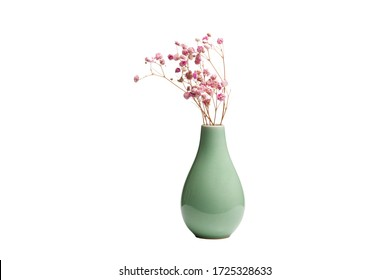 Dried decorative pink flowers in greenish ceramic vase isolated on white background. Macro and close-up.