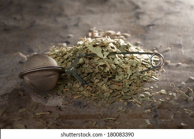 Dried Eucalyptus Tea Tea and tea-strainer on a metal texture