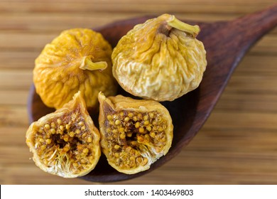 Dried fig fruit cut in half showing seeds on dark wooden spoon on wood background