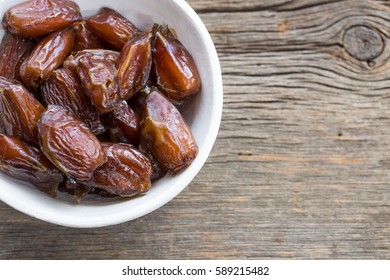 Dried figs in a bowl with copy space over wooden background.