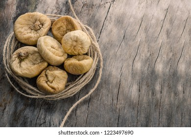 Dried figs in twine on grey wooden table.