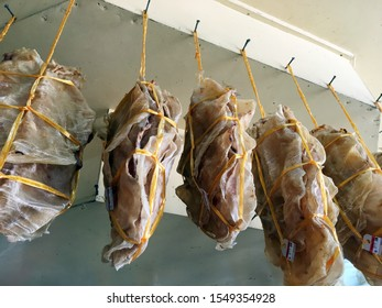 Dried fish maw tied into several bundles for sale, hanging from above, in a local fish market.