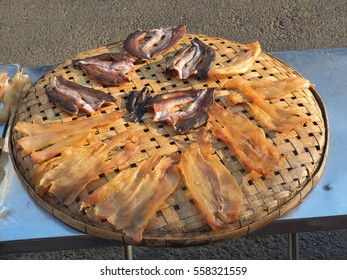 Dried fish on the bamboo grid in the sunny day , Dried fish dry in sunlight. Dried fish is dry foodstuff, this food product by mix salt with fresh fish and then place them under sunlight