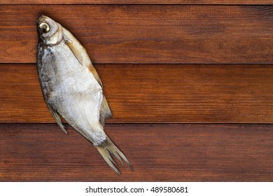 dried fish on a light brown wooden background with empty space