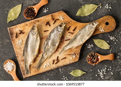Dried fish with salt and pepper on the kitchen cutting board, view from the top