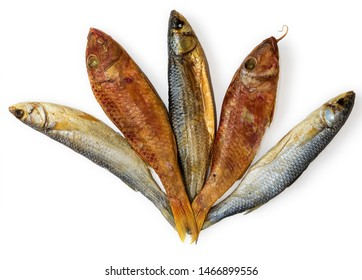 Dried fishes - Mullus and  Mugil - on the table. Salty dry  fish on a white background. Dead dry salty fish - snack to beer. Isolated on white. Soft focus