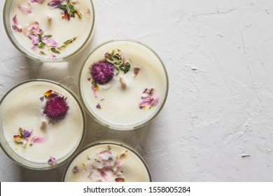 dried floral roses candles with rose quartz crystals on white background