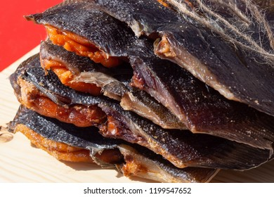 Dried flounder. A stack of dried flatfish with caviar on a light wooden background