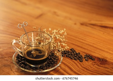 Dried flowers, black coffee cup on wooden table