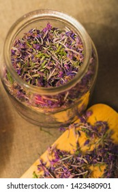 dried flowers of fireweed in a glass jar on a table with a linen tablecloth