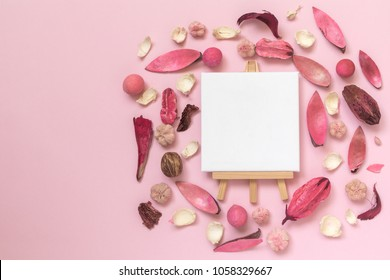 Dried flowers, leaves and plant parts with easel for artists and blank canvas on pastel rose background minimal creative art flat lay concept.