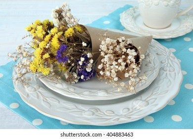 dried flowers on the plate near the Cup on wooden background