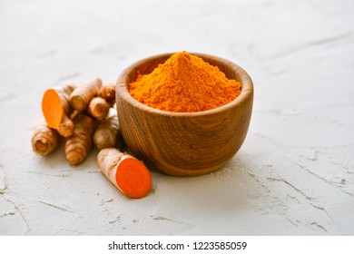dried, fresh and powdered turmeric in bowls on gray background