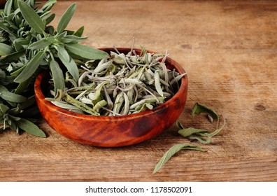 dried and fresh sage over wooden background