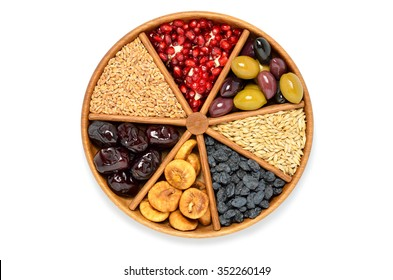 Dried fruits, barley, wheat, olives, pomegranate on wooden plate - symbols of judaic holiday Tu Bishvat .White background. Top view