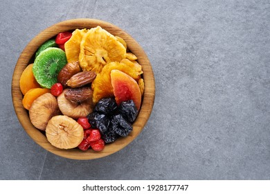 Dried fruits and berries on a wooden bowl top view. Raisins, kiwi, cherries, plums, dried apricots, dates, pineapples, figs, melon. - Shutterstock ID 1928177747