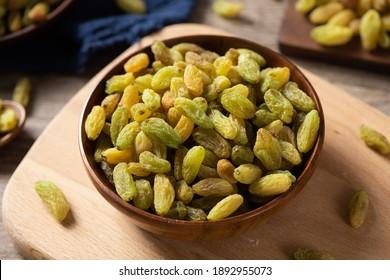 Dried fruits, green raisins in saucer on wooden table.