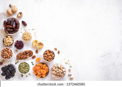 Dried fruits and Nuts in bowls on white background, top view, copy space. Healthy snack - assortment of organic dry fruits and various nuts.