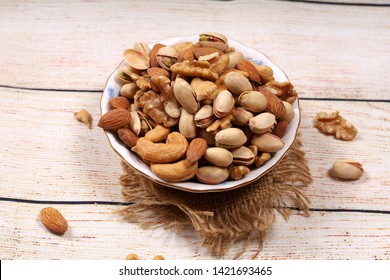 Dried fruits and nuts mix in a bowl on wooden base