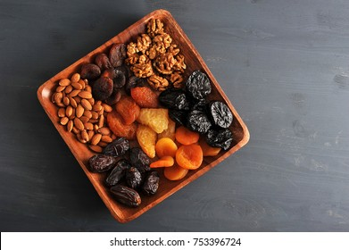 Dried fruits and nuts in a plate. On the plate there are dates, prunes, dried apricots, dried pears and peaches, almonds and walnuts. A dark background. View from above. Close-up. Macro photography.