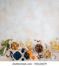 Dried fruits, nuts and pumpkin seeds on beige background with blank space for text; top view, flat lay